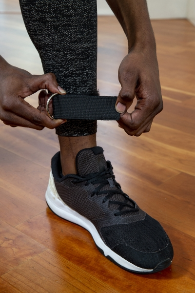man setting up resistance bands on legs